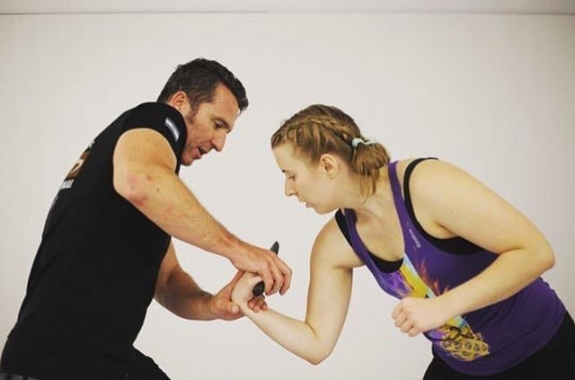 An instructor teaching a student how to use Krav Maga for self defense